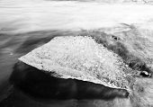 Beautiful beach in the South of Iceland with a black lava sand is full of icebergs washed by the sea. Black and white with a long exposure