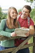Couple On Hike Through Countryside Looking At Map