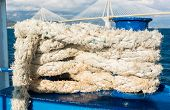 stock photo of bollard  - Rope fastened on a metallic onboard bollard along a ferry broadside - JPG