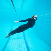 Female Diver Flying Underwater In Swimming Pool