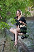 Charming young brunette woman in black dress and high heels sitting on brick wall