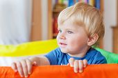 pic of daycare  - Funny little baby boy playing in colorful playpen indoors - JPG