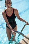 Attractive Happy Female Swimmer On Ladder At Edge Swimming Pool