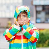 image of rainy season  - Funny smiling little boy walking in city through rain wearing colorful rain coat and green boots outdoors at rainy day - JPG