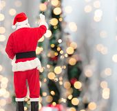 christmas, holidays and people concept - man in costume of santa claus writing something from back over tree lights background