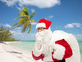 christmas, travel, holidays and people concept - man in costume of santa claus with bag making hush gesture over tropical beach background