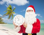 christmas, travel, holidays and people concept - man in costume of santa claus with clock showing twelve over tropical beach background