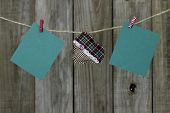 Blank green Christmas cards and plaid fabric heart hanging on clothesline