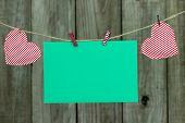 Christmas card envelope with candy cane striped hearts hanging on clothesline