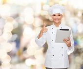 cooking, holidays, technology and people concept - smiling female chef, cook or baker with tablet pc computer showing thumbs up over lights background