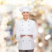 cooking, technology and people concept - smiling female chef, cook or baker with tablet pc computer over holidays lights background