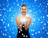 holidays, christmas and people concept - laughing woman in evening dress holding something over blue snowy background
