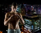 sport, competition, strength and people concept - young man in fighting or boxing position over night city background