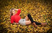 stock photo of short skirt  - Beautiful elegant woman with red blouse and short skirt posing in park during fall. 