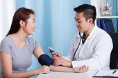 Asian Doctor Measuring Patient's Pressure