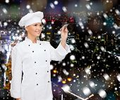 cooking, holidays, advertisement and people concept - smiling female chef, cook or baker with marker writing something on virtual screen over snowy night city background