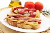 a plate with somme espardenya, typical sandwich in Catalonia, Spain, with grilled vegetables and anchovies