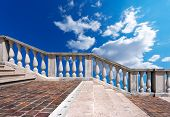 stock photo of porphyry  - Staircase in white stone and marble with balustrade on blue sky with clouds - JPG