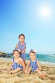 Vertical shot of three cute babies posing on a beach on a sunny summer day