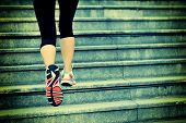 sports woman running up on stone stairs
