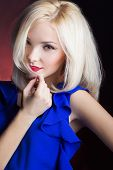 elegant beautiful girl blonde with red lips in a blue dress in the Studio