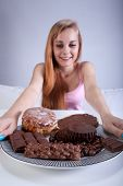 picture of skinny girl  - Young skinny girl holding a plate of sweets - JPG