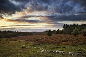 Beautiful Autumn Fall Sunset Over Forest Landscape With Moody Dramatic Sky