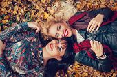 Two Women Head To Head Lying In The Leaves