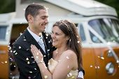 foto of campervan  - Happy just married couple in an orange classic camper van parked outside in a green field ready for camping and a piknick - JPG