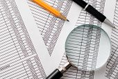 Magnifying Glass, Pen And Pencil On Top Of Reports
