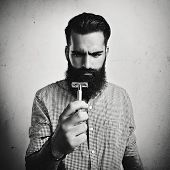 B/w Portrait Of Brutal Bearded Man Looking At Vintage Razor