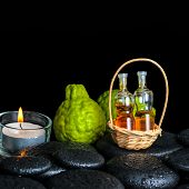 Aromatic Spa Concept Of Bergamot Fruits, Candle And Bottles Essential Oil In Basket On Zen Black Sto