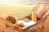 Woman in hammock on sunny beach