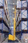 Yellow Forklift Raises Palletising On Top Shelf Of The Rack.