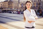 Beautiful brunette business woman in white suit with tablet in her hands outdoors. copy space
