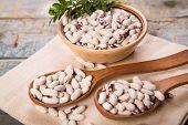 stock photo of kidney beans  - white dry kidney bean in dish on white textile - JPG