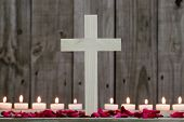 Wood cross by candlelight and rose petals with rugged wooden background