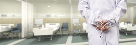 pic of hospital gown  - rear view of a male doctor with stethoscope in hospital ward - JPG