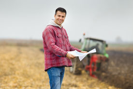 stock photo of land development  - Happy young farmer with forms for bank loan standing on field tractor in background - JPG