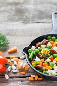 picture of lenten  - Mixed vegetable meal in old iron frying pan closeup and ingredients on wooden rustic table - JPG