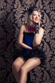 stock photo of cabaret  - beautiful cabaret woman posing on a chair against retro wallpapers - JPG