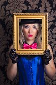 image of cabaret  - beautiful cabaret woman posing with golden frame against retro wallpapers - JPG