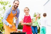 picture of bbq food  - Father and daughter barbecue meat spits and sausages at family garden BBQ  - JPG