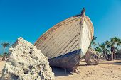 pic of wrecking  - White boat wreck lying on the sand - JPG