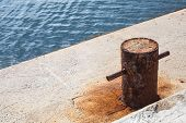 image of bollard  - Old rusted mooring bollard on concrete pier Black sea coast - JPG