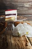 image of cream puff  - piece of cake with a cream puff on a glass base on the old wooden background - JPG