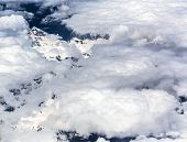 image of snow clouds  - White Clouds on peaks covered with snow - JPG