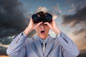 picture of binoculars  - Suprised businessman looking through binoculars against blue and orange sky with clouds - JPG