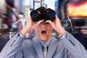 foto of binoculars  - Suprised businessman looking through binoculars against global technology background in blue - JPG