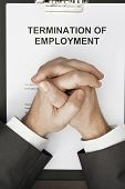 stock photo of terminator  - man with clasped hands over termination of employment document - JPG